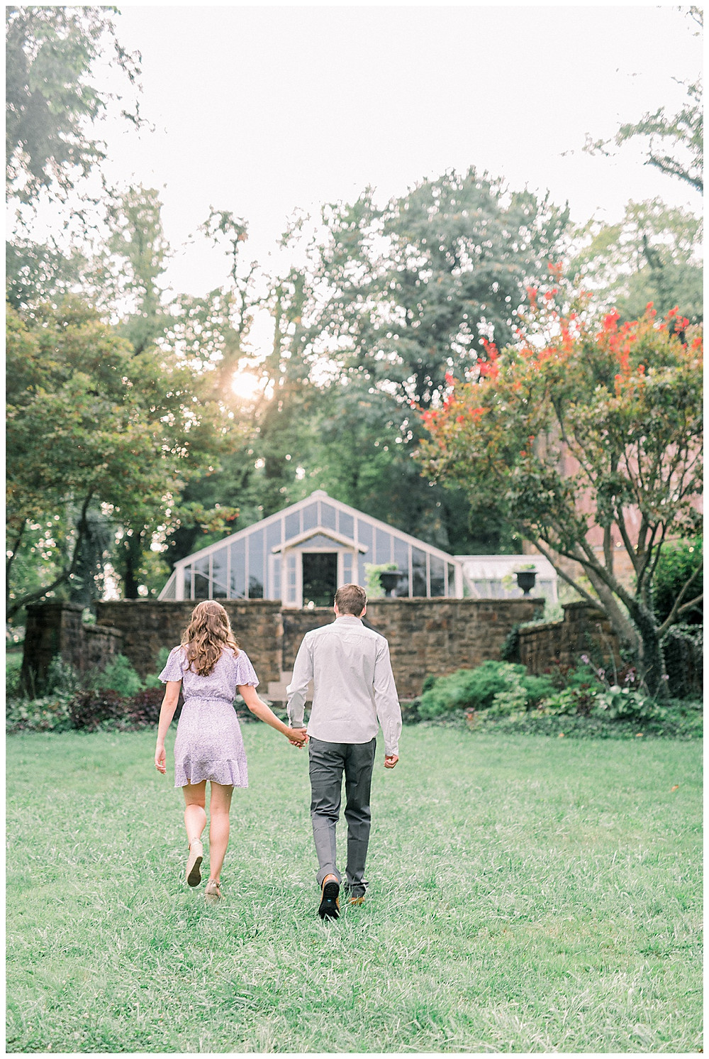 An engaged couple walking through Historic Shady Lane in late summer