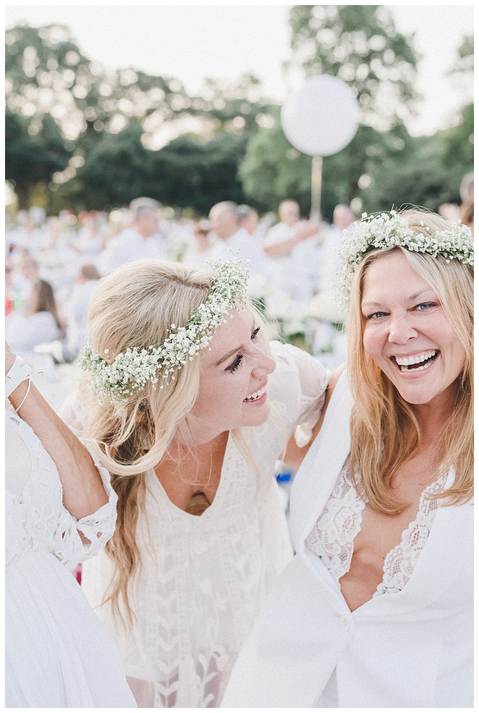 Flower crowns, white dresses, women laughing. Streamers released, portrait of young woman, large white balloons, red lipstick, flowers in her hair, white dress.  Fete en Blanc (Party in White) Lancaster 2019 at Longs Park by Angela Weiler Photography - Fine Art Wedding and Lifestyle Photographer in Lancaster Pennsylvania.