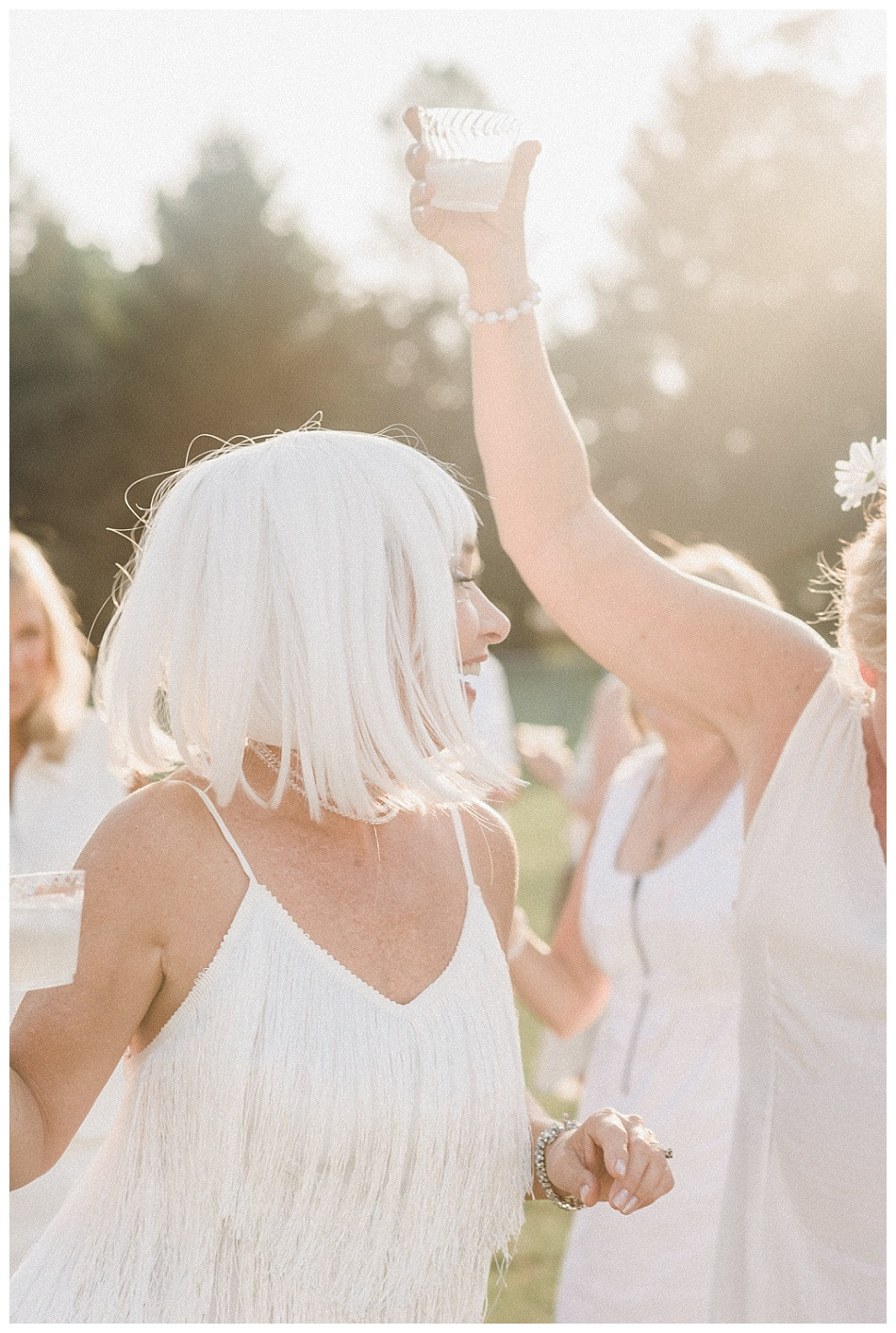 White dress and wig, raised plastic glass.  Fete en Blanc (Party in White) Lancaster 2019 at Longs Park by Angela Weiler Photography - Fine Art Wedding and Lifestyle Photographer in Lancaster Pennsylvania.
