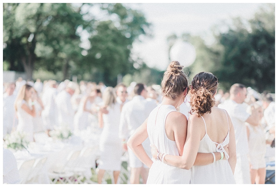 Two girls embrace, shot from behind. Fete en Blanc Lancaster 2019 at Longs Park by Angela Weiler Photography.