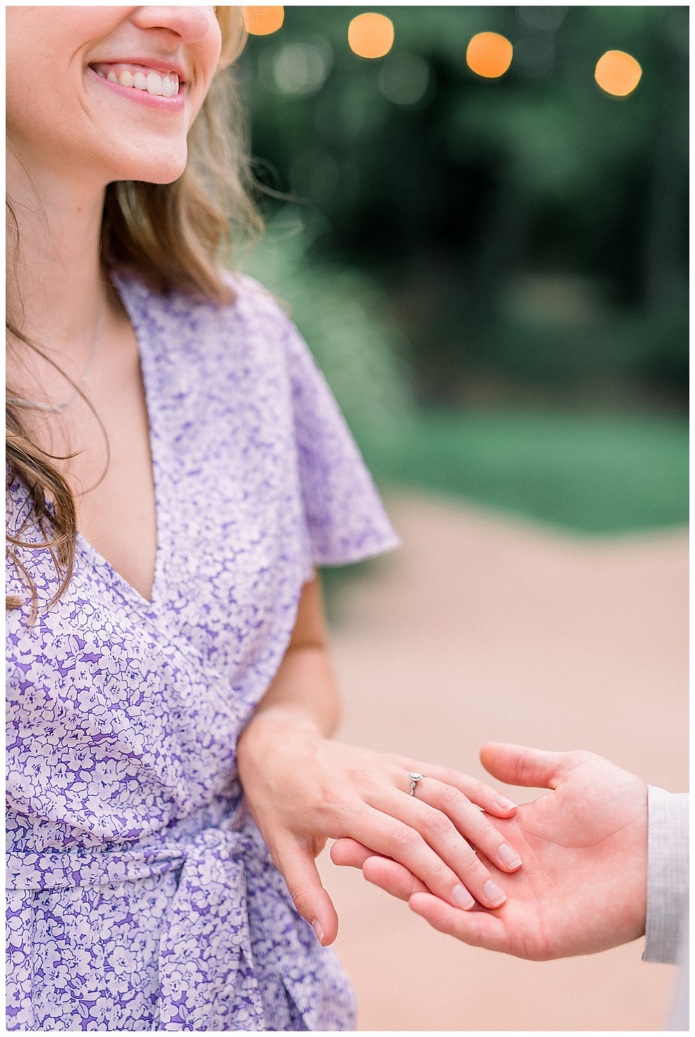 Woman holding fiancé's hand and showing engagement ring
