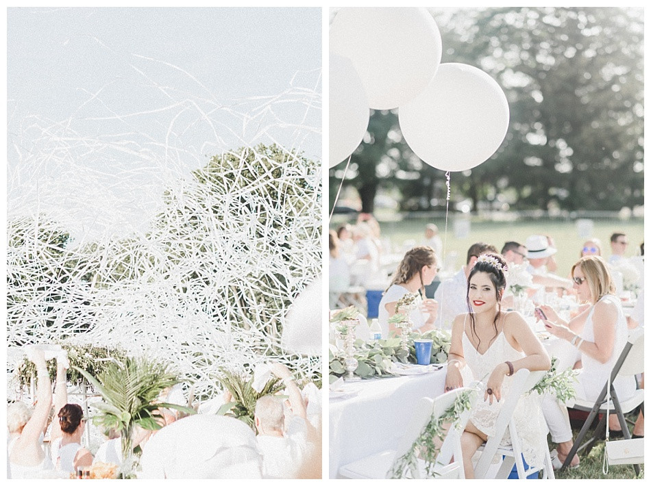 Streamers released, portrait of young woman, large white balloons, red lipstick, flowers in her hair, white dress.  Fete en Blanc (Party in White) Lancaster 2019 at Longs Park by Angela Weiler Photography - Fine Art Wedding and Lifestyle Photographer in Lancaster Pennsylvania.
