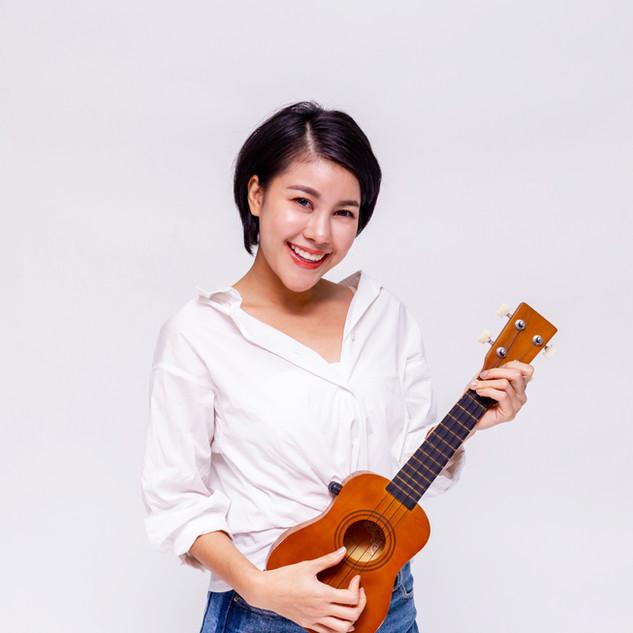 Young Asian female girl playing ukulele