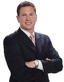 Realtor Chris Handy, Smiling With His Arms Crossed Against A White Background