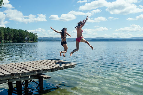 Two girls in bathing suits jumping from