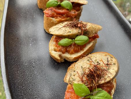 Crostinis mit Tomatenconfit, Genova Bratwurst und frischem Basilikum