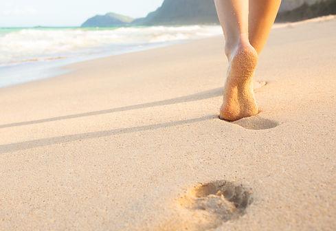 Woman walking on sand beach leaving foot