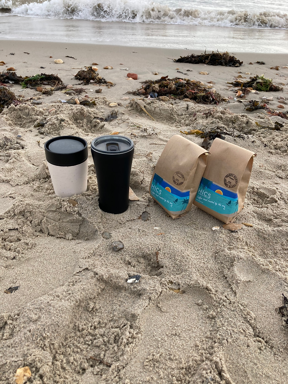 Coffee travel cups beach sand