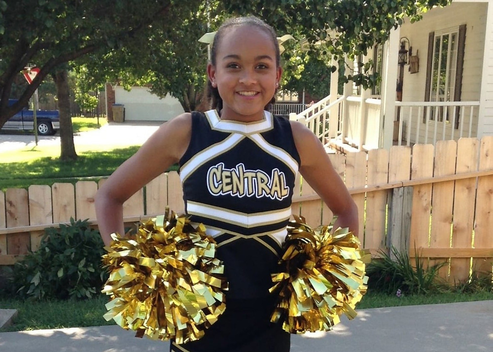 Child in cheerleader outfit