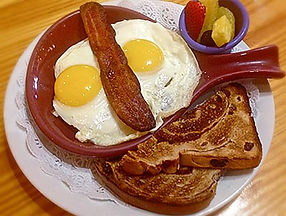 Breakfast skillet with sunnyside up eggs, bacn, toast, and fresh fruit