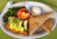 Steamed spinach topped with grilled tomatoes, sliced avocado, with fresh fruit, toast, and egg on the side