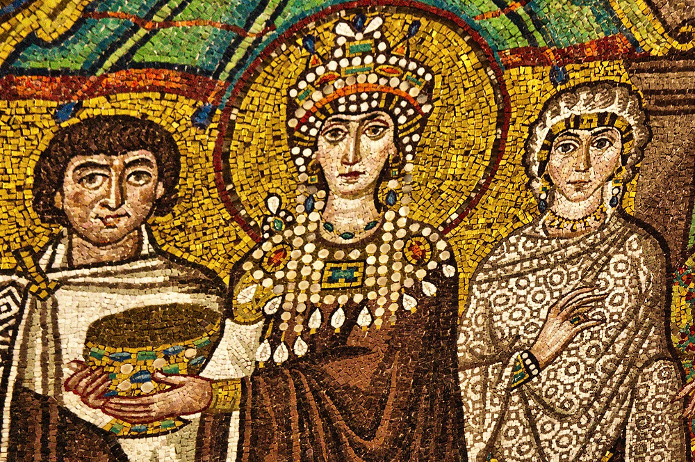 The mosaic of Empress Theodora at the Basilica of San Vitale, Ravenna, Italy - the image shows a woman with an elaborate jewelled crown and jewelled shoulder decoration, flanked by a man on the left and a woman on the right. The central woman holds a jewelled large cup or bowl, the background is gold and the three figures are dressed in whites and browns