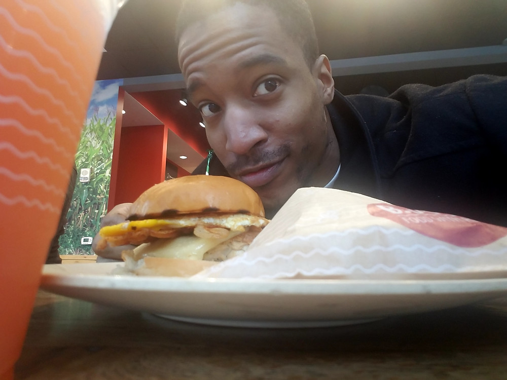 Darkfox Photography smiling behind a chicken and egg burger from B,Good in Raleigh, North Carolina