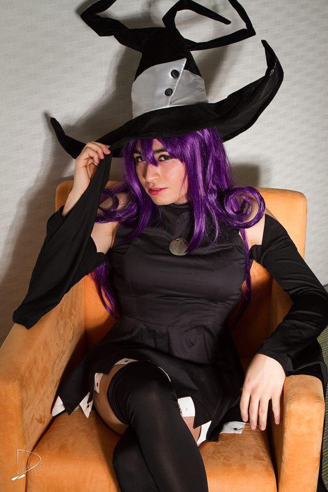 Man in Blair cosplay from soul eater sitting on an orange chair