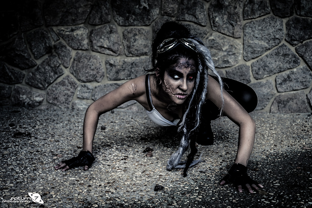 Woman with white out contacts crouched low to the ground in front of bricks on gravel
