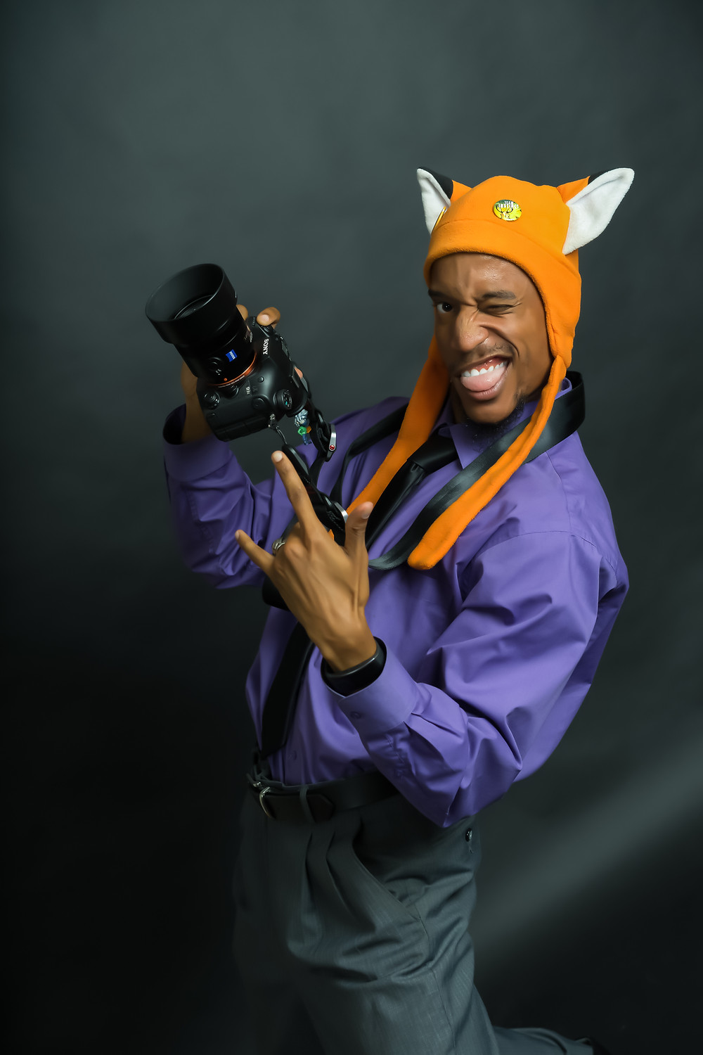 Darkfox Photography posing with a camera with his tongue sticking out and a rocker pose