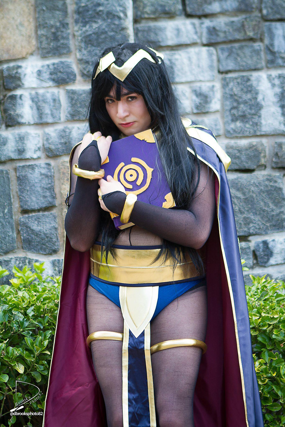 Man dressed up as Tharja from Fire Emblem clutching a magical book
