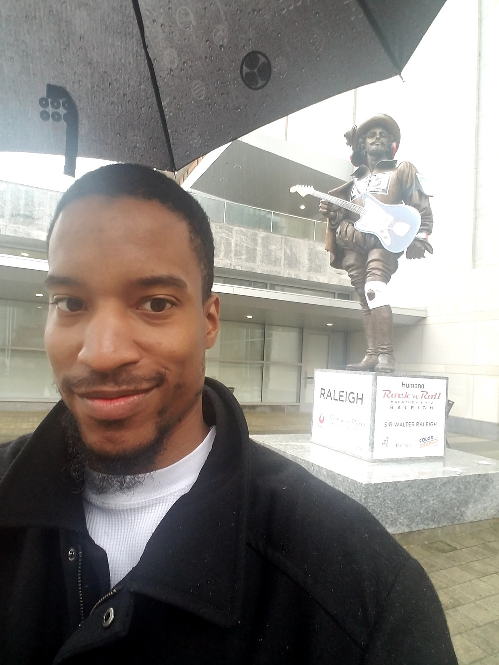 Darkfox Photography standing under an umbrella in front of a statue of a rock and roll marathoner in Raleigh, North Carolina