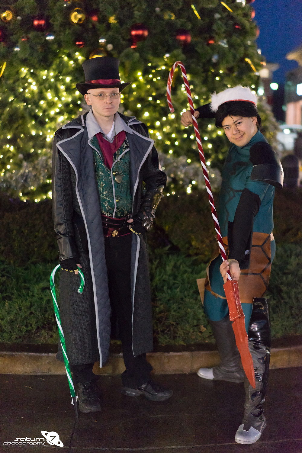 Two cosplayers dressed up in front of a glowing Christmas tree