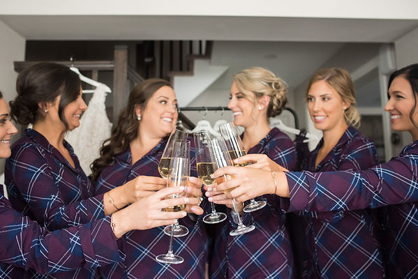 Bride and bridesmaids doing a cheers
