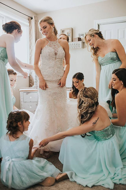 bride in her gown with her bridesmaids