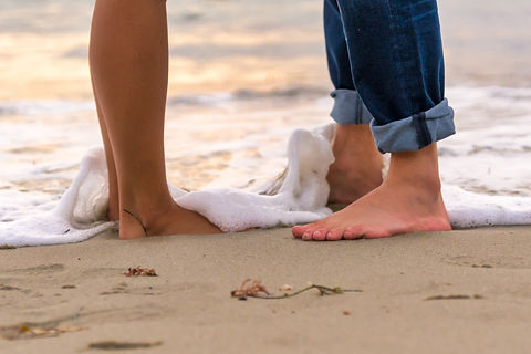 couple dipping feet in sea on beach without shoes