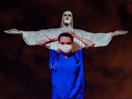 Rio de Janeiro's 'Christ Statue' Illuminated With Portraits of Healthcare Workers and flags.