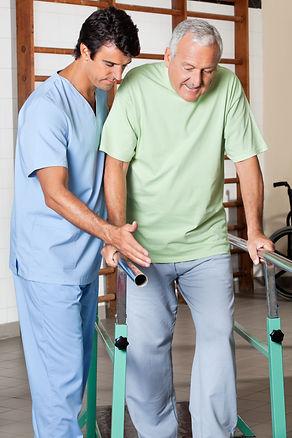 Physical therapist assisting senior man