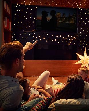 familie i stuen ser en film med en hyggelig opsætning med stjerner