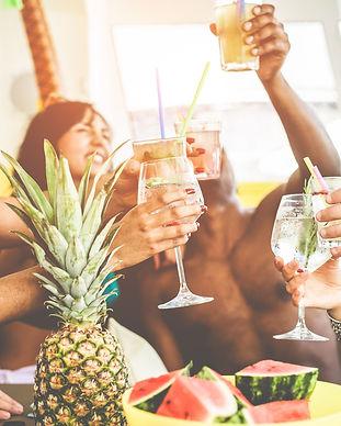 Indendørs fest med unge mennesker, frugt og drinks