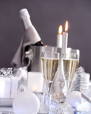 Nytårsbord med to champagneglas, lys og champagne