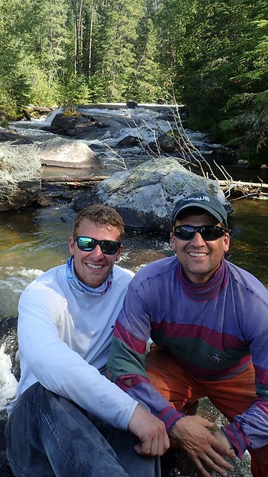 Patrick Kucera with his son Joey smiling with shades on over the creek
