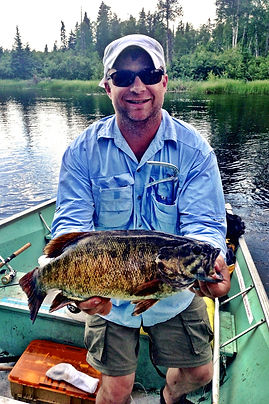 Chris Pulley holding a 14 inch Walleye in a fishing boat with shades on