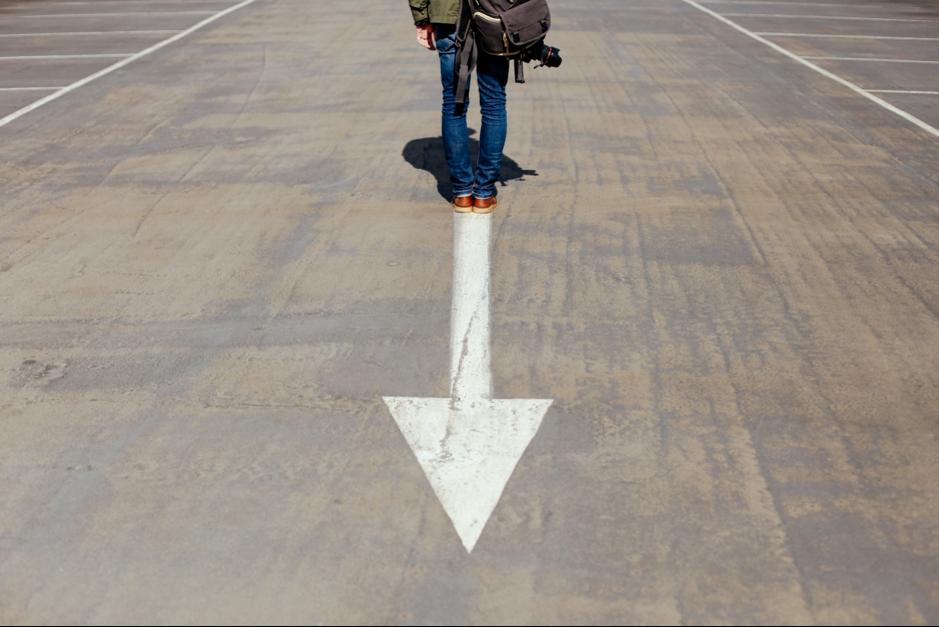 man standing on arrow