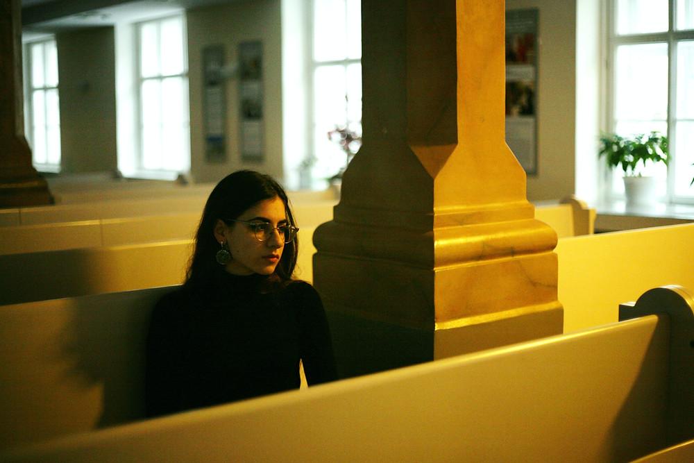 Woman sitting alone in an empty church.