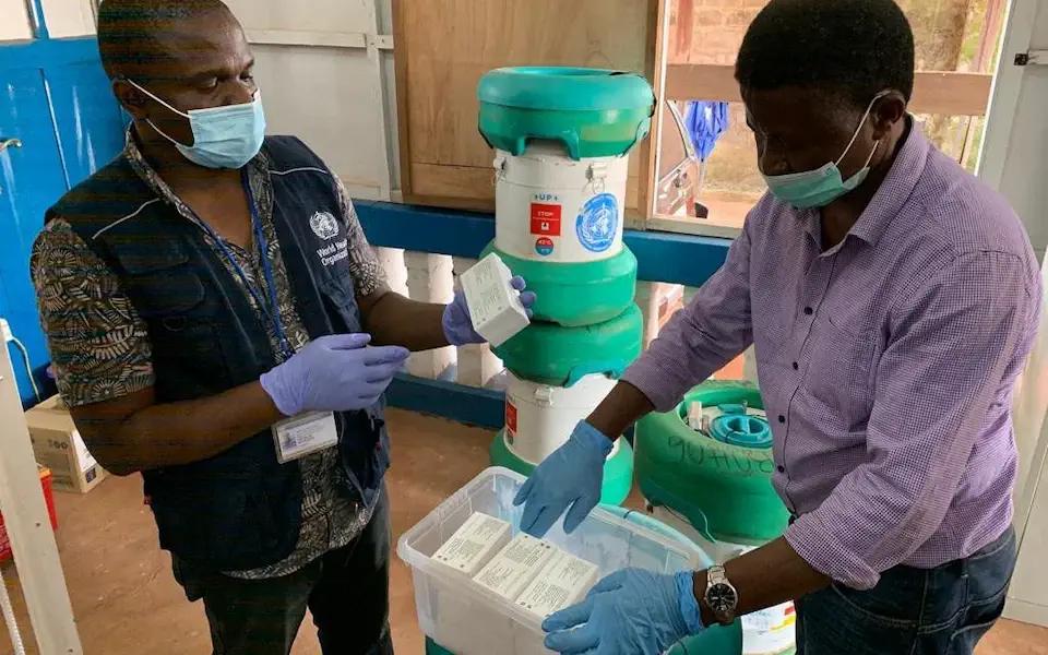 Volunteers storing vaccines in Arktek freezer