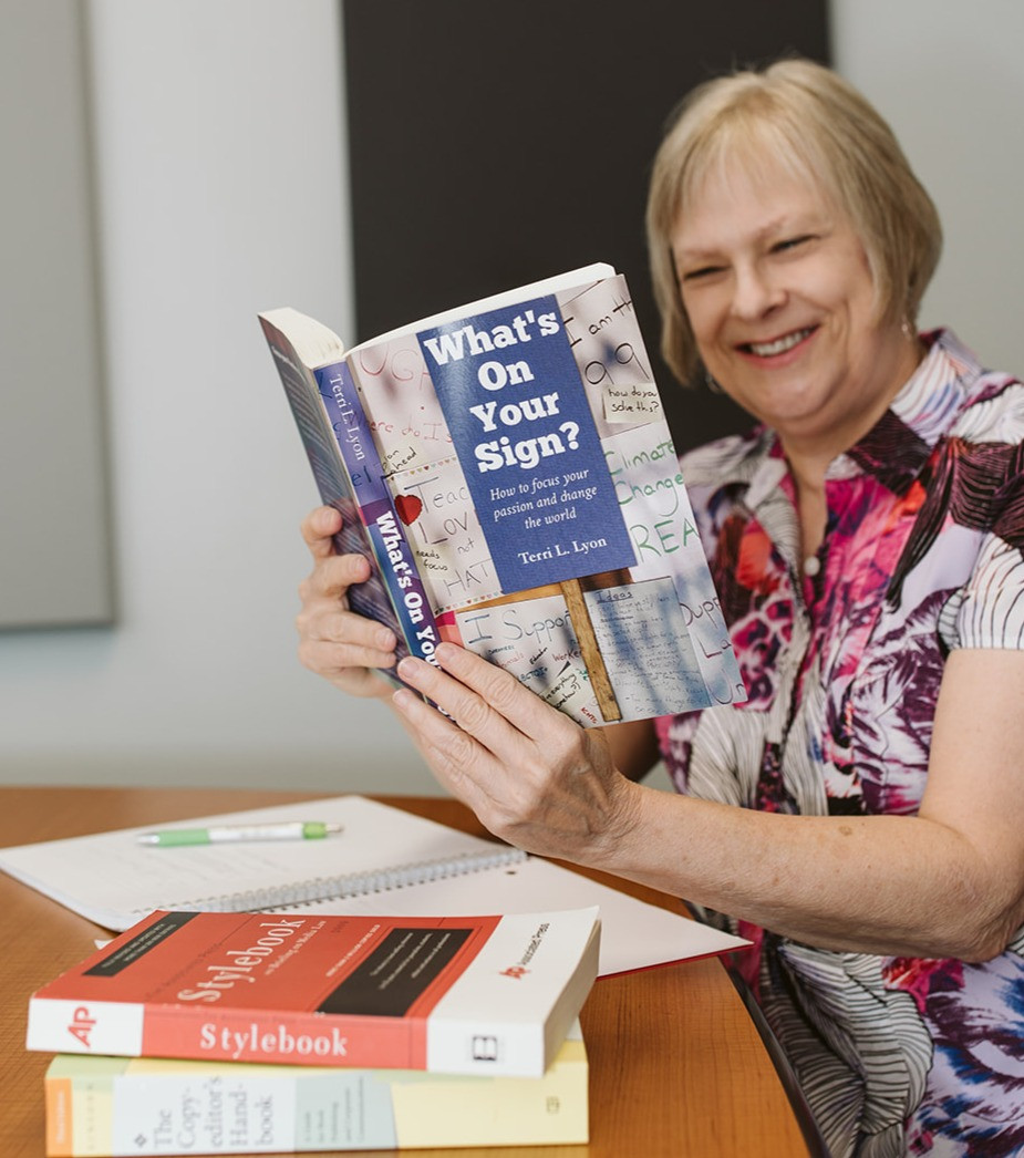 The author and editor is smiling while holding up a copy of a book she edited.