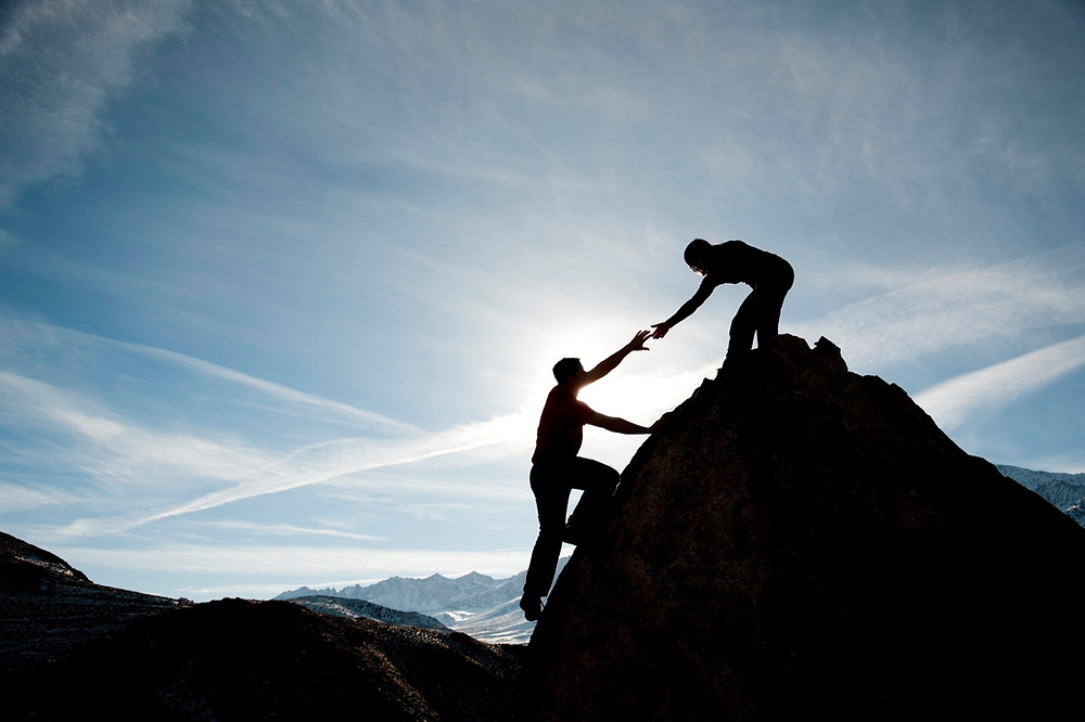 A man on a hilltop extending his hand to another man climbing up