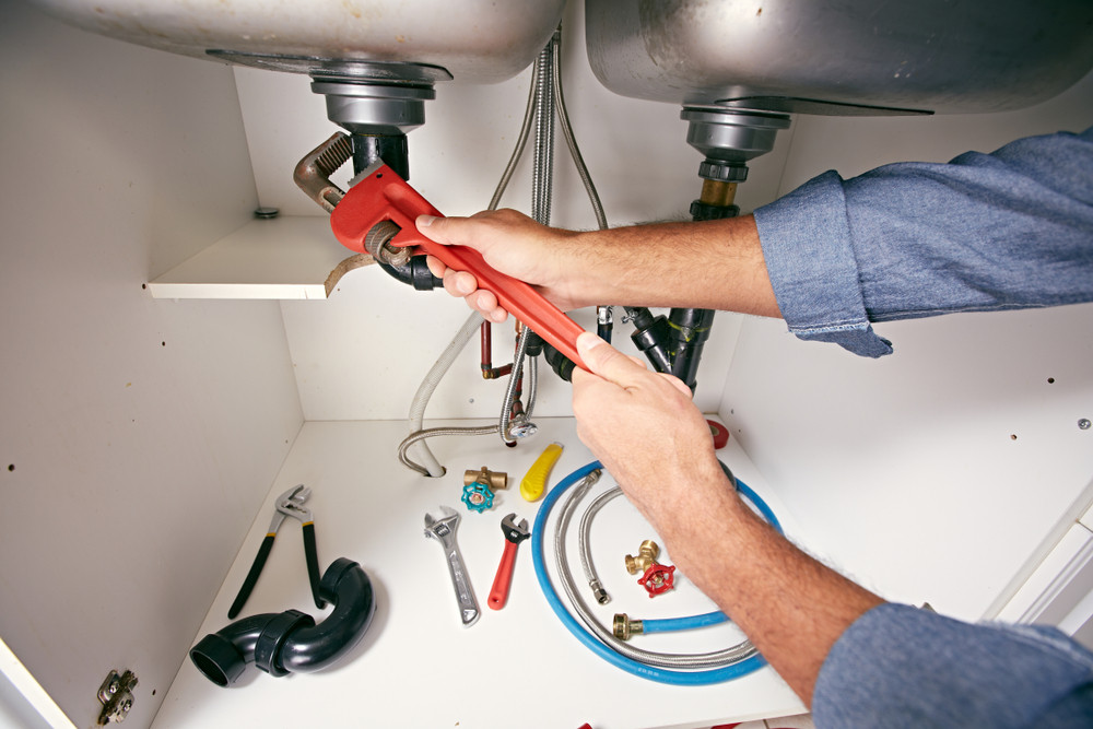 A plumber's hands holding a wrench and working on a drain pipe.