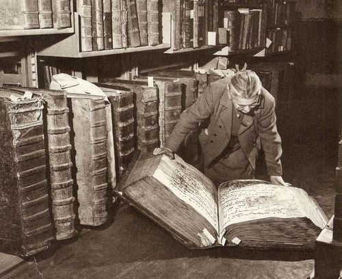 Vintage black and white photo of woman on the floor reading a giant book.