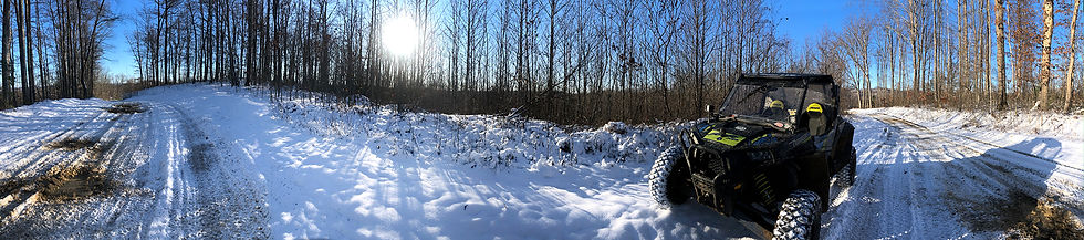 Panoramic photo of snowy trails and ATV on sunny day.