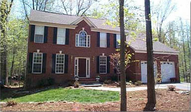 Clifton House Bob Designed & Built. Two car garage, black shutters on a brick home in the woods.
