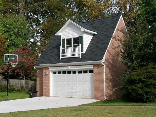 Garage Addition Bob Designed & Built. Single garage door on a standalone garage made of brick.