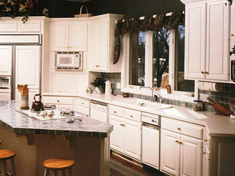 White kitchen with white countertops and cabinets. Custom island.