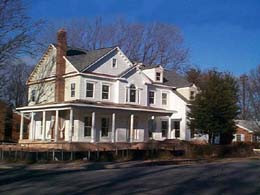 North Arlington House Bob Designed & Built. White house with a wrap around porch on an open road.