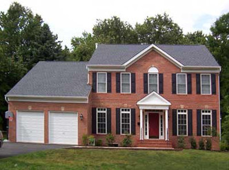 Fall Church Home Bob Designed & Built. Two car garage, black shutters on a brick house with a red door.