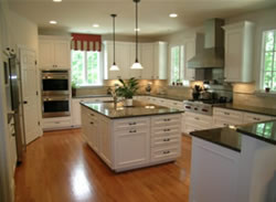 Custom island with white cabinets and gray countertops.