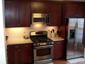 Darker cabinetry with stainlesss steel appliances.