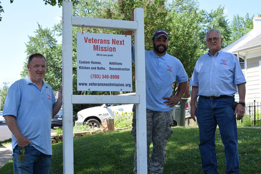 VNM Crew standing by a VNM sign on a job site.