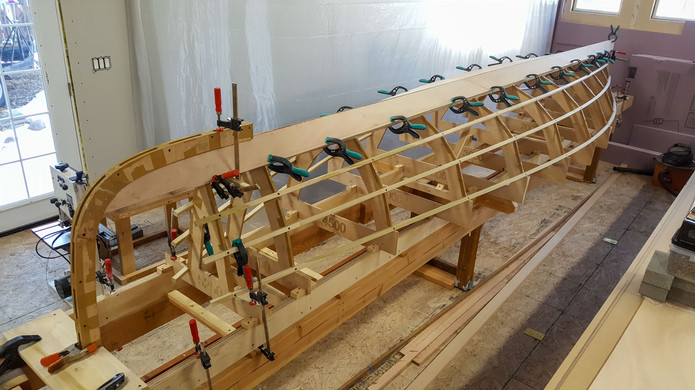 Garboard Planks glued to keelson and clamped to the first stringers.